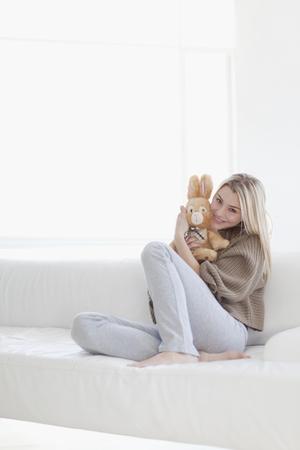 love seat: Teenage girl hugging stuffed toy LANG_EVOIMAGES