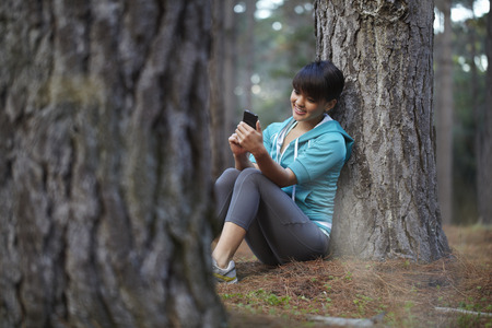Runner using cell phone in forest