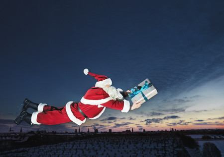 sunrises: Santa Claus flying with wrapped gift