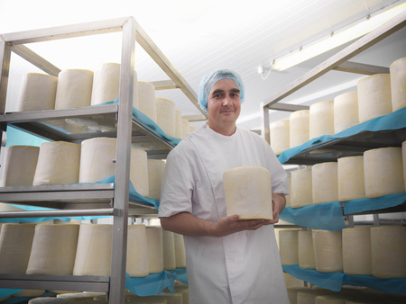 large group of business people: Worker holding cheese in factory LANG_EVOIMAGES