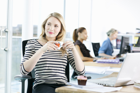 wasting away: Businesswoman drinking coffee at desk
