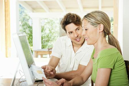 remuneraciÓn: Couple reading bills together LANG_EVOIMAGES