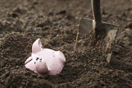 Shovel digging up piggy bank LANG_EVOIMAGES