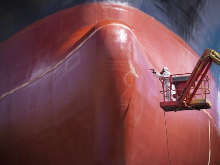 spewing: Worker painting ship's hull