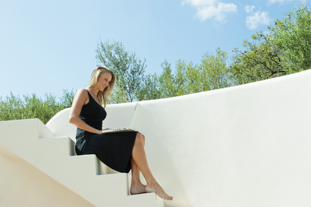 Woman using laptop on steps outdoors LANG_EVOIMAGES