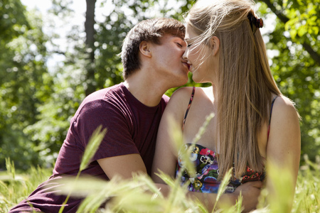 Teenage couple kissing in tall grass