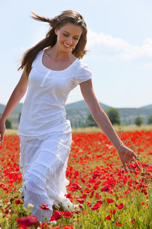 Woman walking in field of poppies LANG_EVOIMAGES