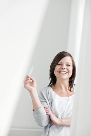 Smiling woman taking pregnancy test LANG_EVOIMAGES