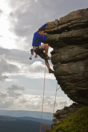 jeopardizing: Rock climber scaling steep rock face LANG_EVOIMAGES