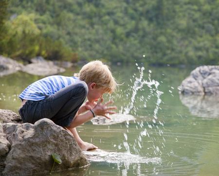 Boy washing his face in still lake LANG_EVOIMAGES