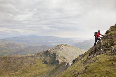 mountainous: Hiker climbing rocky mountainside