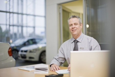 Car salesman sitting at desk in showroom