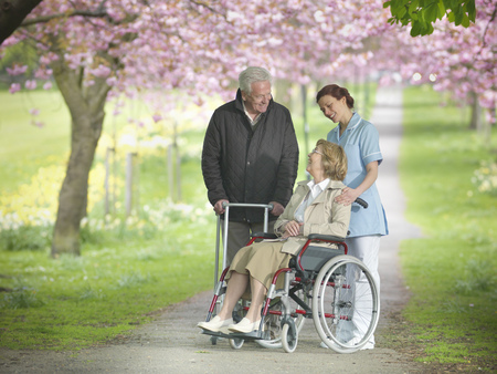 matured: Older couple with caretaker in park LANG_EVOIMAGES
