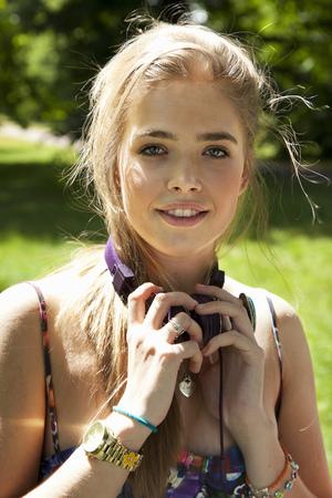 Teenage girl wearing headphones outdoors LANG_EVOIMAGES
