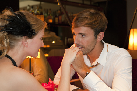 attractiveness: Man kissing girlfriend in restaurant