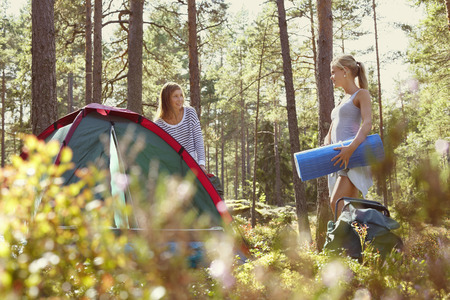 coverings: Women setting up campsite in forest