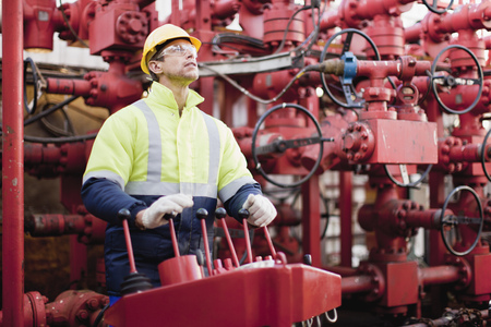 power operated: Worker operating machinery on oil rig LANG_EVOIMAGES