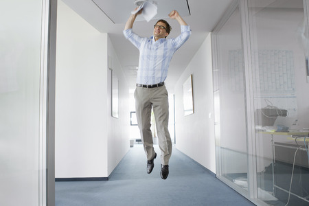 low spirited: Businessman jumping for joy in office