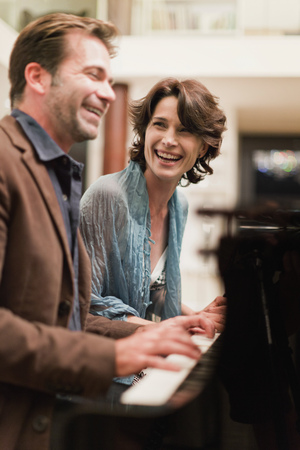 musically: Couple playing piano together at home