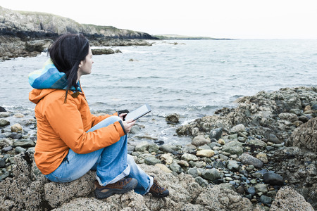 viewed: Woman reading on rocky beach