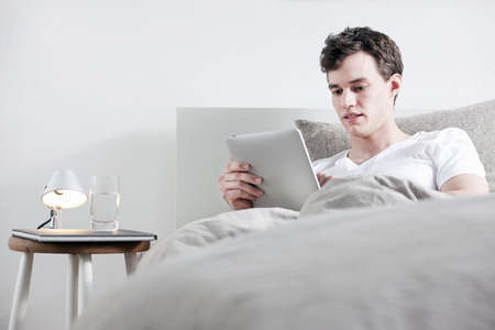 lays down: Man using tablet computer in bed LANG_EVOIMAGES