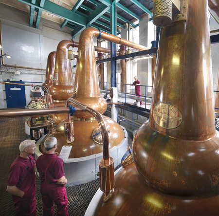assessed: Workers checking stills in distillery
