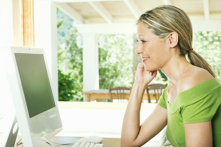teleworking: Woman using computer at desk LANG_EVOIMAGES