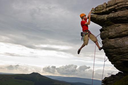 Rock climber scaling steep rock face LANG_EVOIMAGES
