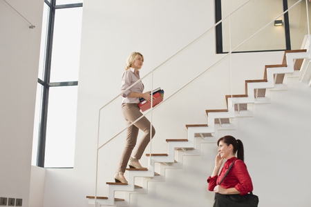 ascends: Businesswoman climbing stairs in office LANG_EVOIMAGES