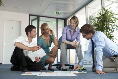 conferring: Businesspeople examining work in office LANG_EVOIMAGES
