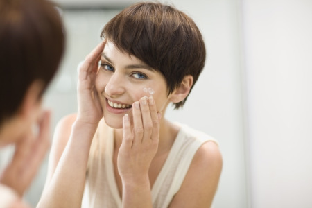 Woman applying moisturizer in mirror