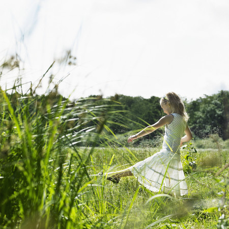 Girl playing in tall grass in field