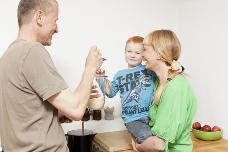 cooking implement: Parents feeding reluctant son in kitchen