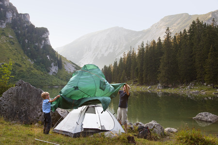 pitching: Father and son pitching a tent by lake LANG_EVOIMAGES