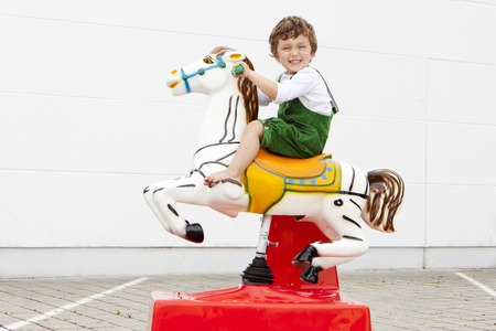 Boy riding mechanical horse outdoors LANG_EVOIMAGES