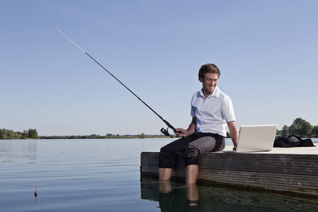 midsummer pole: Man fishing and using laptop on dock LANG_EVOIMAGES