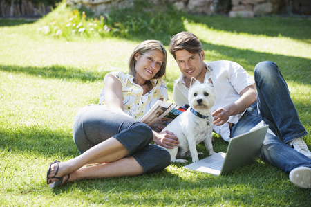 Couple relaxing with dog in grass