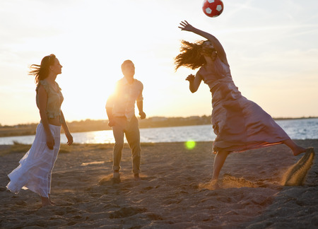 tosses: People playing with soccer ball on beach