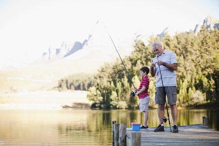 midsummer pole: Boy fishing with grandfather in lake