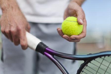 rehearse: Older man holding tennis ball and racket