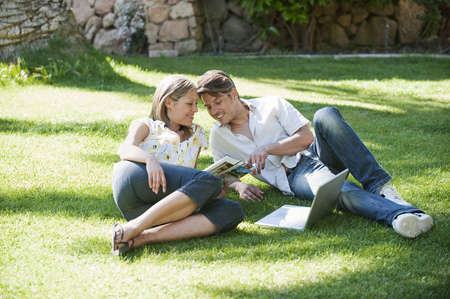 Couple relaxing together in grass LANG_EVOIMAGES