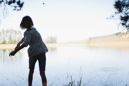 tosses: Girl skipping stones in lake LANG_EVOIMAGES