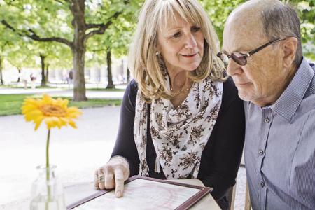 Older couple reading menu at cafe