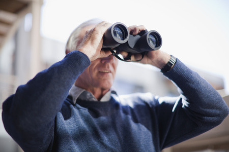 detects: Businessman looking through binoculars