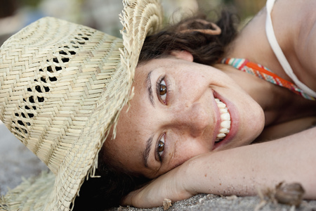 lays down: Close up of smiling woman wearing sunhat