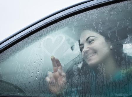 drizzling rain: Teenage girl drawing on wet car window
