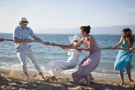 Newlyweds and guests playing tug of war LANG_EVOIMAGES
