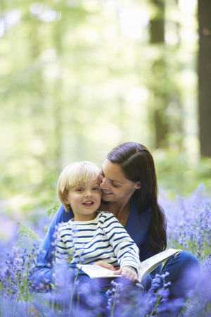 tomes: Mother and son reading in forest