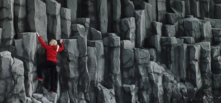 ascends: Woman climbing basalt columns