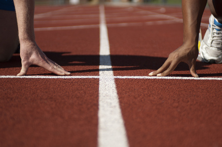 Close up of athletes hands on track
